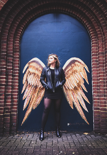 Student standing in front of wings in London photo