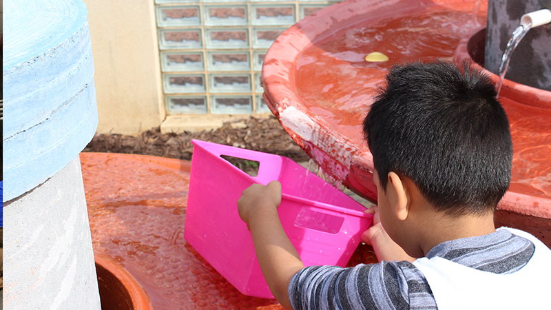 child enjoying water table