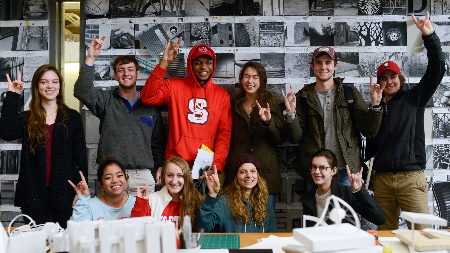 Students posing together in front of critique wall