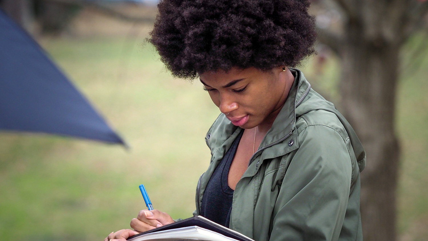Student taking notes during an outdoor class