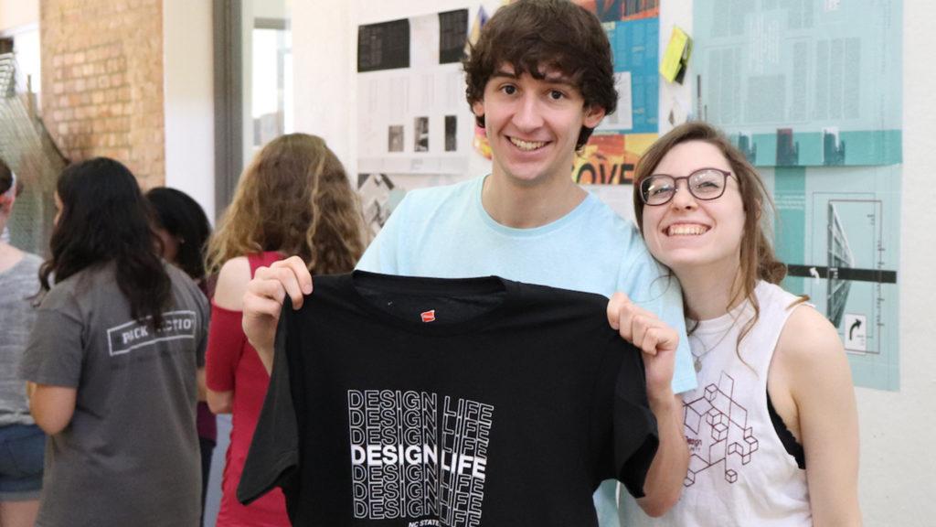 Students hold up DesignLife tshirt